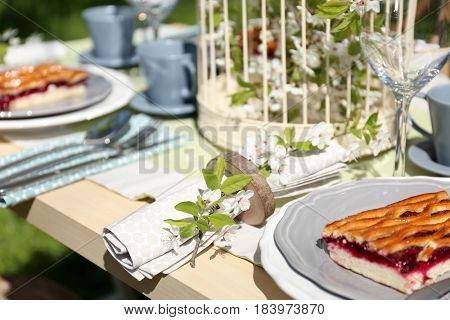 Napkin with branch of flowers in holder on served table
