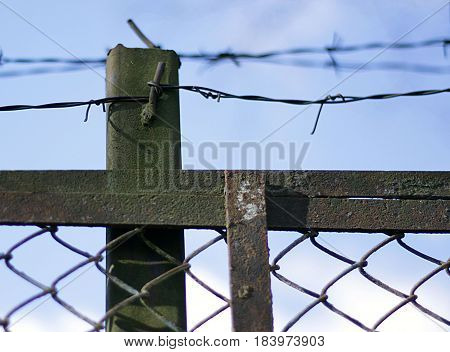 Barbed wire over an old rusty dirty fence. Against the blue sky. Protection of civilians from criminals. Close up