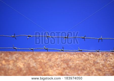 Barbed wire on rusty gates in prison, against the blue sky.