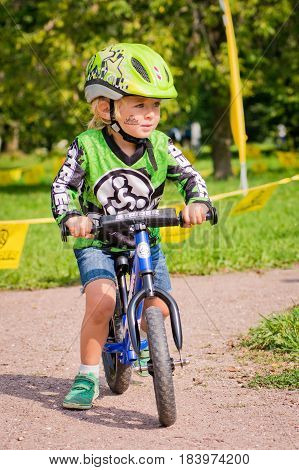 Russia. Moscow. Vorontsovsky Park on the 21st of August. STRIDER CUB 2016. Little boy on balancebike and helmet