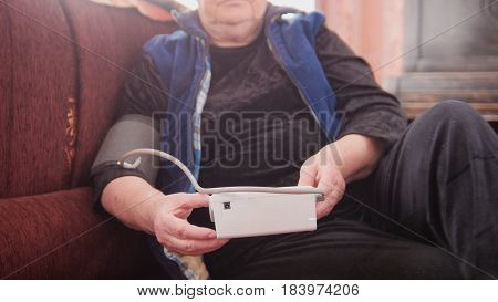 Mature lady checks her health state with manual manometer - measures pressure - pensioner alone at home, middle shot