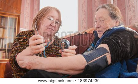 Two pensioners - checking health state with manometer - measures pressure, pensioners healthcare, close up