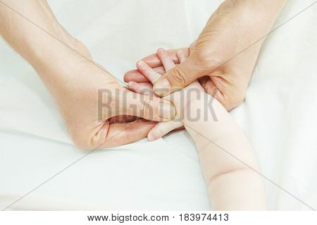 Masseur massaging a child hand