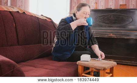 Senior lady - elderly woman at home drinking from a mug - pension life, midle shot