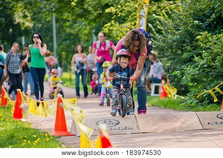 Russia. Moscow. Vorontsovsky Park on the 21st of August. STRIDER CUB 2016. Baby Racing on the balance bike. Mum helps the child to pass an obstacle