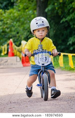 Russia. Moscow. Vorontsovsky Park on the 21st of August. STRIDER CUB 2016. Child on balancebike and helmet