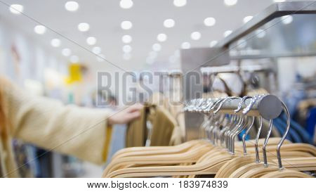 Woman in a clothing store chose a dress - shopping concept, close up