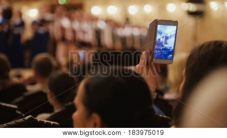 Audience in concert hall during performing piano girl- people shooting performance on smartphone, music opera, telephoto