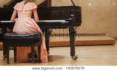 Close up view of cute teenager girl plays piano in the concert hall at scene, telephoto