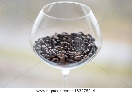 Coffee beans in wine glass on white background