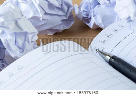 Paper balls and pen over blank white sheet - Creativity crisis concept