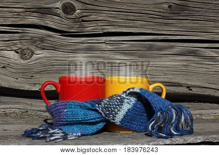 Red and yellow mug wrapped in a scarf on the background of a very old wooden surface / warming atmosphere near the house