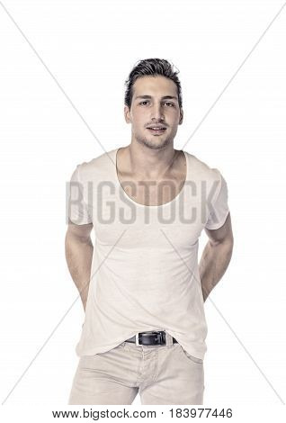 Brown eyed, black haired latin man standing in studio, looking to a side, hands in pockets, isolated on white background