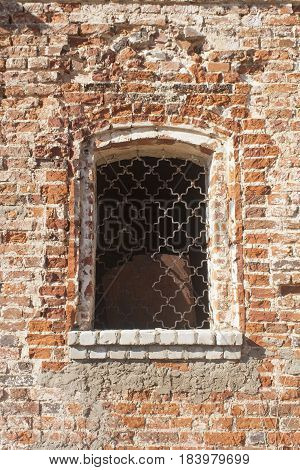 shot of barred window in a dilapidated brick wall