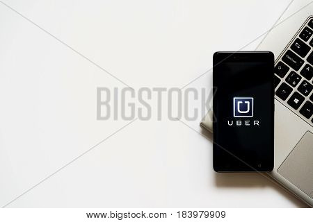 Bratislava, Slovakia, April 28, 2017: Uber logo on smartphone screen placed on laptop keyboard. Empty place to write information.