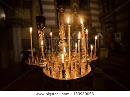 A lot of burning candles with shallow depth of field in the orthodox church, religion concept
