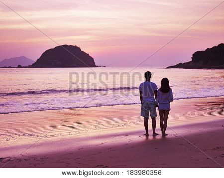 young asian couple taking a walk on beautiful beach before sunrise.