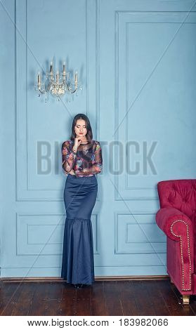 beautiful woman to the utmost in a classical interior a blue wall an ancient chandelier a claret sofa
