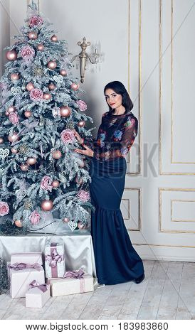 the beautiful woman costs near a New Year's tree in a classical interior Christmas