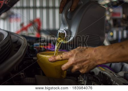 Car mechanic fills a fresh lubricant engine oil at car garage for maintenance a car poster