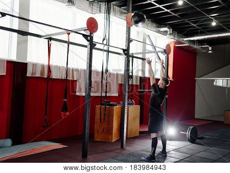 Muscular man doing exercise with medicine ball in gym. Young man doing upper body exercise working out with heavy weighted ball