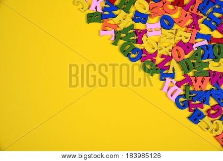 Multicolored wooden letters of the English alphabet are lined with an angle on the yellow surface an empty space in the left part