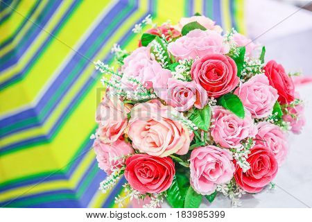 Wonderful clay art woman hand hold bouquet of roses flower in pink on white background beautiful artificial flowers of craftsmanship with skillful