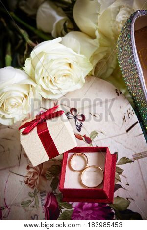Decorative setting of gift wrap box with 2 golden rings, white roses bouquet and bridal shoe