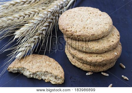 Fresh integral cookies and wheat on a dark background