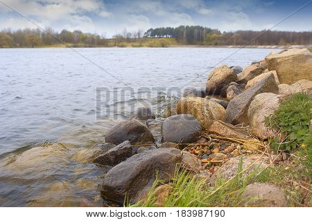 Landscape of beautiful nature outdoors in a park on a sunny afternoon. The water sparkles, the stones are colorfully poured on the shore. The atmosphere of rest from everyday hassle. Travel and tourism.