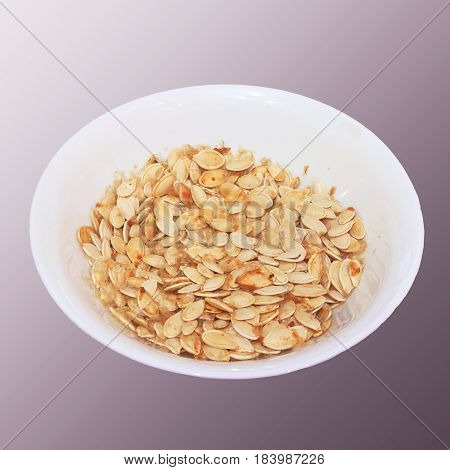 Plate with dried white sunflower seeds isolated on a gray background. Seeds of zucchini dried in a plate
