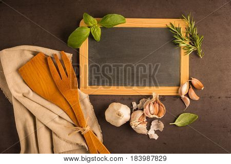 Blackboard for your text fresh garden herbs on stone table. Basil garlic and rosemary. Cooking ingredients. Top view with copy space