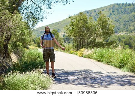 Hitch-hiking traveler with a blank cardboard sign on a mountain road. Budget travel. Auto stop