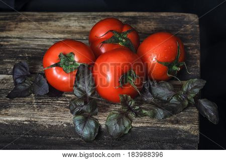 A top view of fresh tomatoes, herbs on an old Wooden table