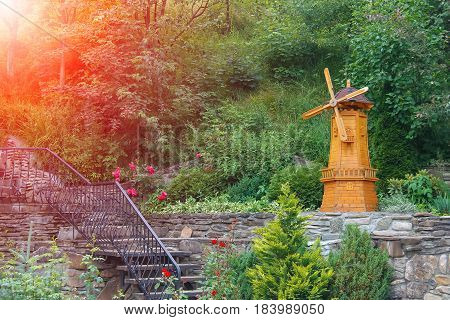 Decorative wooden mill in city park in sunlight