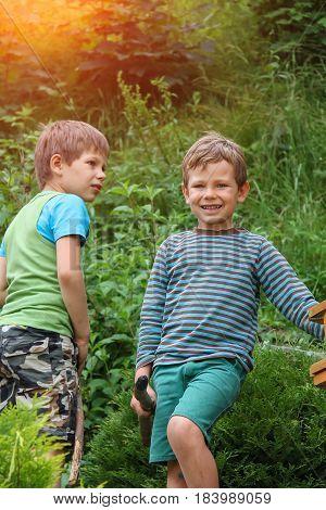 Two boys in summer city park in sunlight