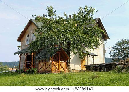 Modern cottage with wooden porch and veranda. Carpathians Ukraine