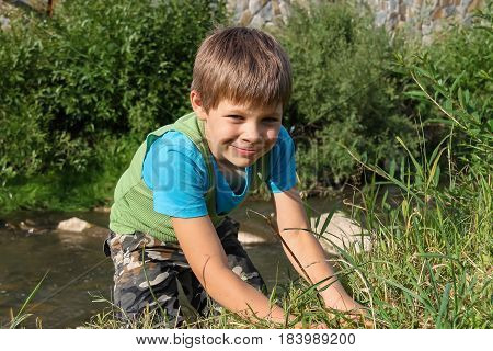 Smiling boy in green grass near small river