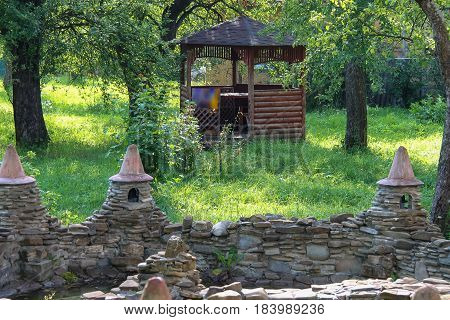 Decorative pond and small wooden pavilion in summer garden