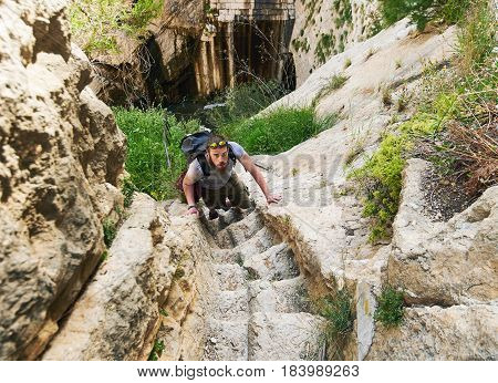 Man traveler climbing up a stepped mountain road. Photo was taken in The Tibi Dam (embalse de Tibi) is a masonry dam on Monegre River in Spain. It is one of the oldest dams in Europe. Spain