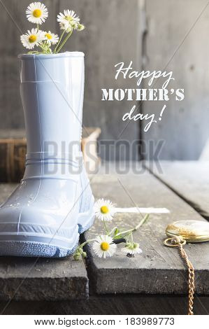 Daisy and boots on a vintage background and text Happy Mothers Day lettering..