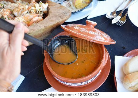 Hot fresh seafood soup on a traditional casserole.