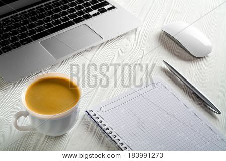 Start of Morning work office desk with a cup of coffee computer laptop notebook pen White wood texture table. Business concept background