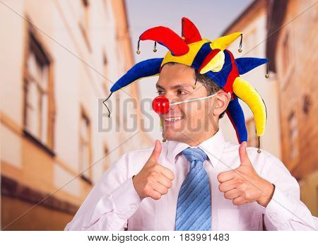 Handsome young businessman with a red clown nose and colorful harlequin hut in his head