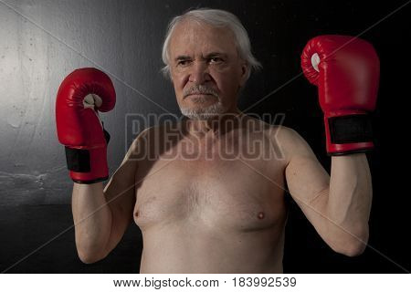 Senior boxer man with red gloves on black wall background