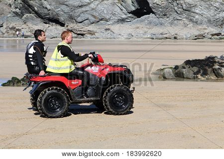 Newquay, Cornwall, Uk - April 2 2017: Two Men In Wetsuits Speed Along The Newquay Beach On A Quad Bi