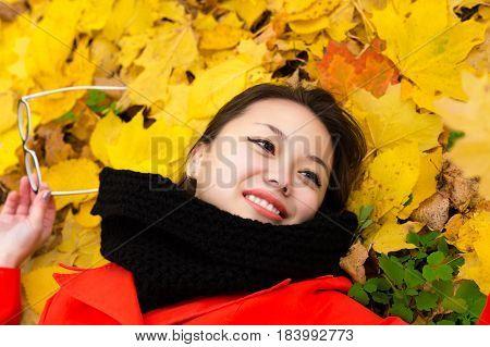 smiling Korean girl with glasses lying on leaves