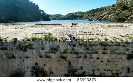 Man traveler sitting on a edge of the dam with hands raised and enjoying the nature and silence. Photo was taken in The Tibi Dam (embalse de Tibi) is a masonry dam on Monegre River in Spain. It is one of the oldest dams in Europe.