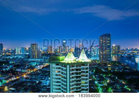 Cityscape Bangkok at night Many building and construction with river and bangkok eye. The top of view on skyscraper. Night street is show to lighting on the road with technical take long exposure