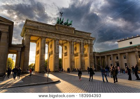 BERLIN, GERMANY - APRIL 16, 2017: Tourists visit the Brandenburg Gate at sunset on April 16, 2017 in Berlin Germany. The Gate a 18th century neoclassical monument is one of the best known landmarks of Germany.